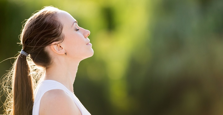 Image of a Calm beautiful smiling young woman with ponytail enjoying fresh air outdoor