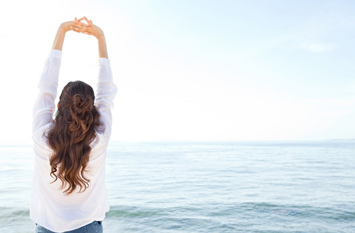 image of a woman stretching her arms up and relaxing in coastal exterior - Healthy wellness nature lifestyle